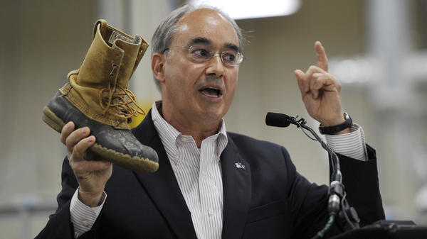 Rep. Bruce Poliquin shows off his 30-year-old L.L. Bean boots during a ceremony at the new production plant in Lewiston, Maine, in August 2017.