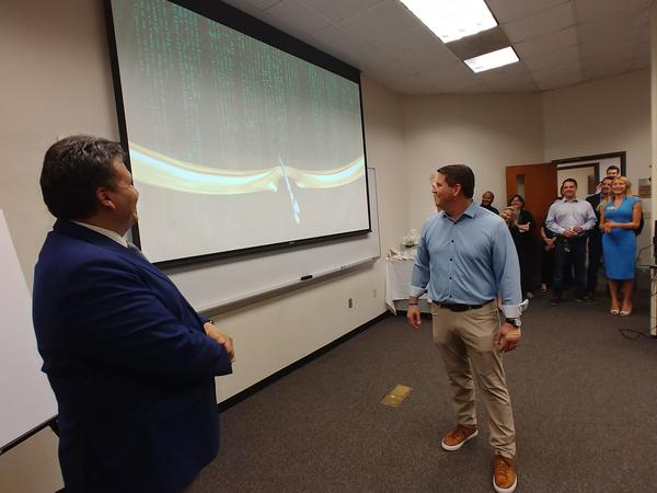 "USF Muma College of Business Dean Moez Limayem, left, and ReliaQuest founder/CEO Brian Murphy hold a ""virtual ribbon-cuttin""..."