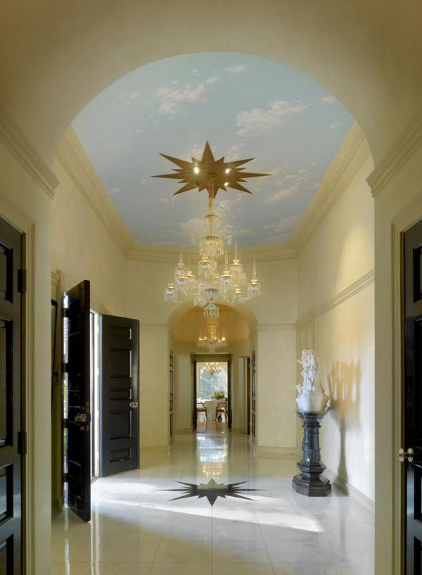 Williams thought a home's entrance should make a statement. In this Colonial Revival residence, designed in Beverly Hills for the Landis family in 1955, the narrow foyer has large double doors that swing open to reveal a high ceiling covered in a <em>trompe l'oeil</em> sky, and a lavish chandelier hung from a starburst medallion. The medallion's design is repeated on the marble floor.