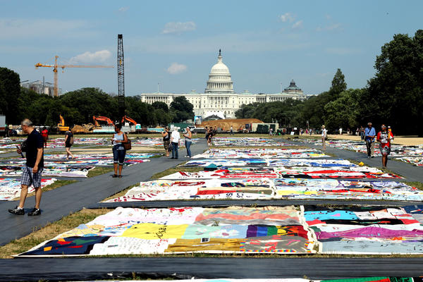 Visitors tour portions of the AIDS Memorial Quilt on display at the National Mall this week.