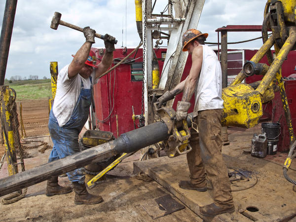 President Obama and Mitt Romney are both calling on the U.S. to become less dependent on foreign oil, though their plans differ. Here, workers with Bramwell Petroleum set up a derrick for a new oil well near Spivey, Kan., in March.