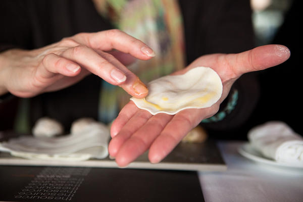 """The dumpling dough circle is brushed with egg yolk in a """"half-moon"""" pattern along the top edge, which is critical to holding the dumpling together when it cooks. """"Your dumpling doesn't have to look perfect. As long as its properly sealed, it will cook up just as good as any other,"""" says Drewno."""