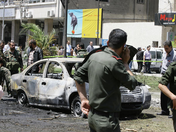 Syrian government security officers after a blast in the Marjeh district of Damascus on Tuesday.