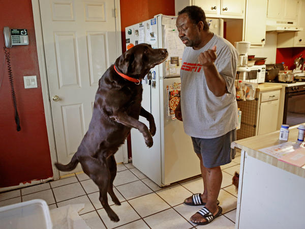 """Mike Jackson and his dog Coco at home in Oklahoma City. He says of his medical costs: """"If anything goes wrong, I'm one step away from disaster."""""""