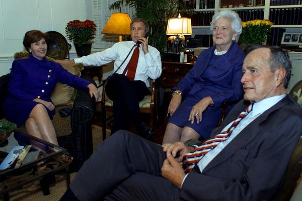 Republican presidential candidate George W. Bush speaks on the phone while watching election returns with his wife, Laura, and parents on election night at the Governor's Mansion in Austin, Texas, on Nov. 7, 2000. Thousands gathered outside the Texas Capitol building to hear Bush speak later in the evening.