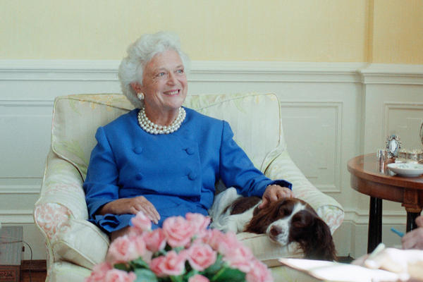 "First lady Barbara Bush, with pet Millie, talks to reporters on Sept. 11, 1990, in the family residence of the White House. Mrs. Bush said Iraq could not be allowed to get away with its occupation of Kuwait. She also revealed that Millie had a case of lupus, but ""she's in complete remission."""