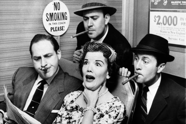 Nanette Fabray gags as railroad commuters Caesar, Carl Reiner (top) and Howard Morris (right) poke their smokes in her direction while looking over her shoulder to read her newspaper, on <em>Caesar's Hour,</em> in 1955.