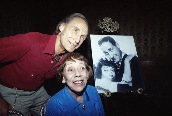 Legendary pair Caesar and Coca pose in a Boston hotel in 1992, near an old photograph of the two of them. They were announcing the Boston opening of their comedy show <em>Together Again. </em>