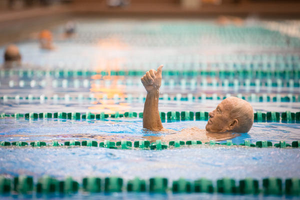 Johnston gives his wife, Janice, a thumbs up after winning his heat of the medley with a time of 1:31:88. He came to the United States on a swimming scholarship at the University of Oklahoma, where he also met his wife.