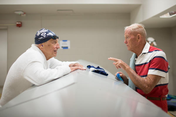 Johnston discusses medications with Burt Bronk, 82, in the locker room. The two didn't compete together, but Bronk won first place in the men's 80-to-84 100-yard butterfly.