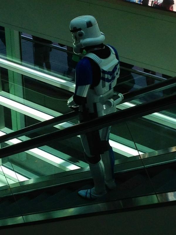 A lone, sad stormtrooper descends an escalator.