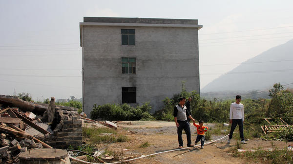 Relatives of He Mengqing walk in front of his house, which the local government has slated for demolition. The rice farmer from Chenzhou in China's Hunan province rejected a government offer of compensation for his land; he set himself on fire when officials came for him.