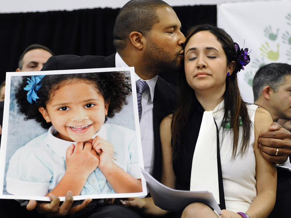 "Jimmy Greene holds a picture of his daughter, Ana, as he kisses his wife Nelba Márquez-Greene, at a January news conference in Newtown, Conn. They try to remember the good days with their daughter. ""It is what brings me great comfort and great joy,"" Márquez-Greene says."