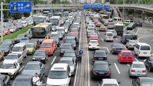 """Drivers step out of their vehicles for a better view while stuck in traffic along Beijing's Second Ring Road on a """"Car Free Day"""" on Sept. 21, 2010. For foreigners trying to drive in car-crazy China, the headaches begin with the written test."""