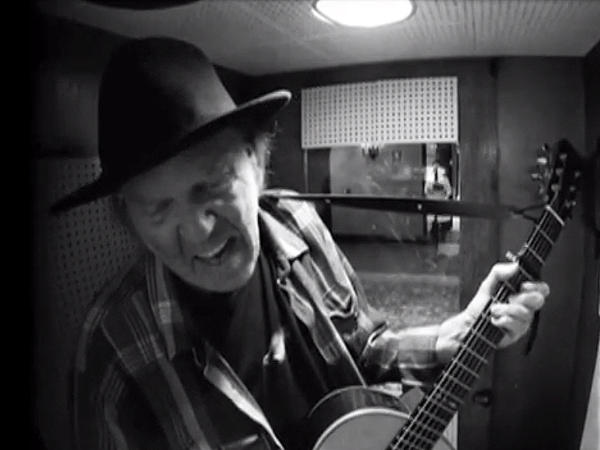 """Neil Young in a recording booth, tracking a cover of Bert Jansch's """"Needle Of Death."""""""