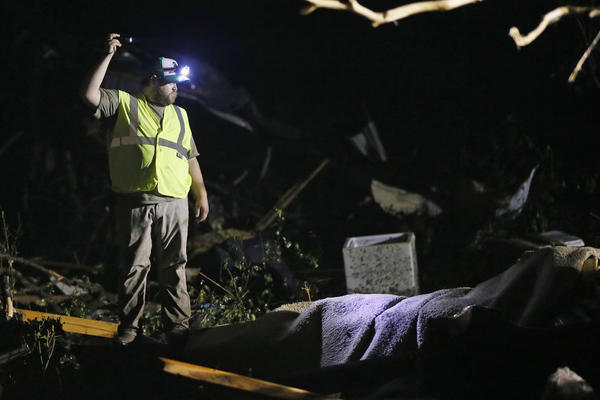An emergency responder shines a flashlight into the remains of several mobile homes as he searches for survivors in Louisville, Miss.