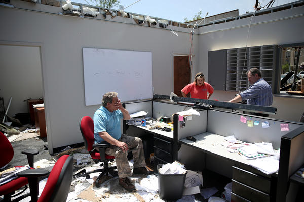 Scott Black (left), Holly Boatner and Paul Flatt salvage what they can from the building where they work in Tupelo after it was destroyed by a tornado. A second day of tornadoes has caused devastation in the South.