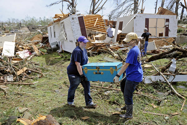 Jodi Walker and Tabitha Russell carry a trunk from a destroyed home in Tupelo, Miss. Tuesday's storms came after tornadoes swept through Arkansas, Oklahoma and Iowa on Sunday and Monday, killing more than a dozen people.
