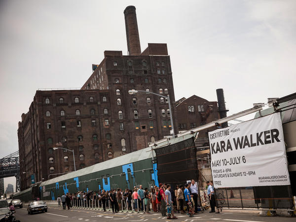 """Visitors wait in line for the Kara Walker exhibit on May 10, opening day. The show was housed in a former Domino Sugar refinery. Inside, visitors described the building as """"cathedral-like"""" and """"creepy"""" and said it smelled like a bakery."""