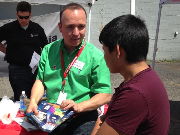 Mario Medrano of the American Red Cross speaks to an attendee about tornado safety at the Children's Day Festival in Oklahoma City.