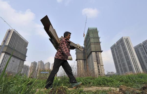 A garbage collector walks past residential and office buildings under construction in Hefei, in China's Anhui province, on April 3. China's economy has grown to the world's second-largest in the years since 1989.