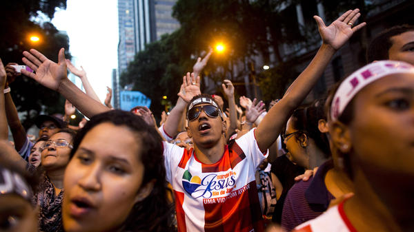 Evangelical Christians hold their hands out in prayer during the annual March for Jesus in downtown Rio de Janeiro, Brazil, in 2013. Evangelicals play an increasingly large role in the nation's politics.
