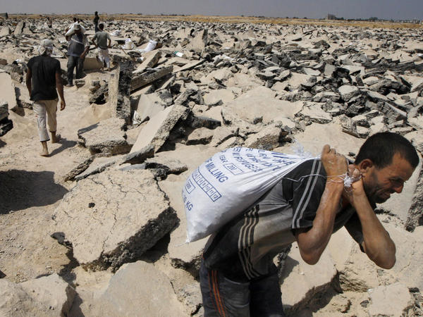 Palestinians dig through the runway in 2010 to collect rubble and gravel needed for construction in the war-ravaged territory.