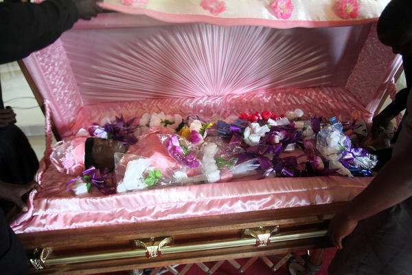 """Family and friends paid final respects to Rebecca """"Mama"""" Barclay by throwing silk flowers in her coffin and taking her picture during services at a Baptist church in Liberia."""