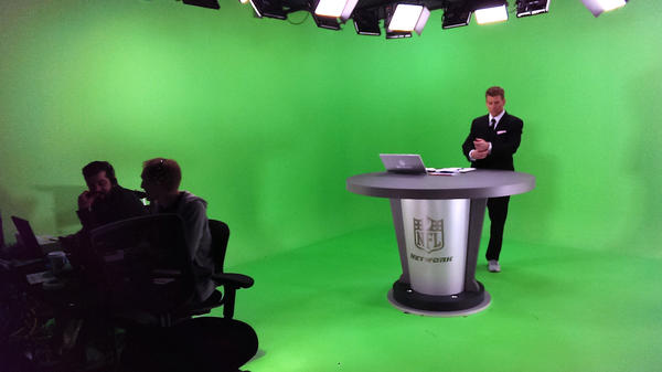 Walking inside the NFL RedZone studio is strange: It's bright green, it's freezing cold, and it's mostly silent. Here, host Scott Hanson prepares for the start of the broadcast.