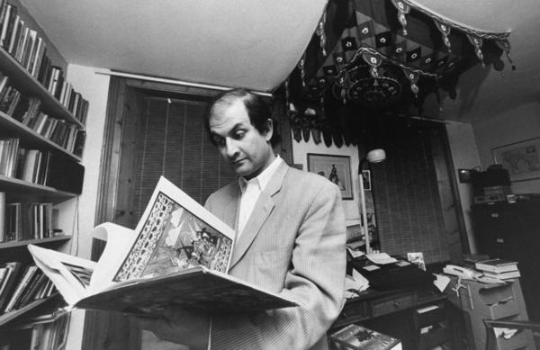 British writer Salman Rushdie leafs through a book in his study. He went into hiding for years after the Iranian leader Ayatollah Khomeini issued a fatwa calling for his death in 1989. The ayatollah denounced Rushdie's portrayal of the Prophet Muhammad in the novel <em>The Satanic Verses</em>.