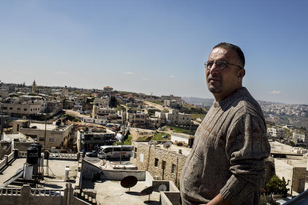 Palestinian Walid Abu Khdair stands on his rooftop, which is directly across the street from the light rail station and the spot where his cousin, 16, was kidnapped and later killed last summer.