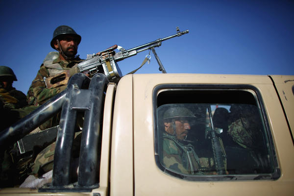 Afghan soldiers at Camp Eagle roll out in a pickup truck mounted with a machine gun for an early morning patrol.