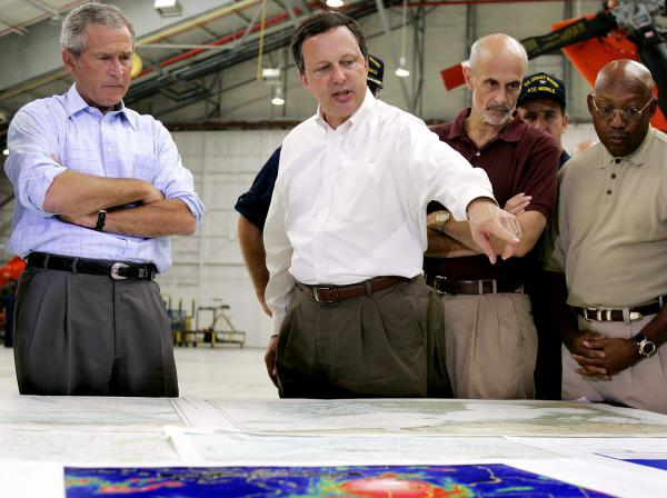 Federal Emergency Management Agency Director Michael Brown (center) briefs President George W. Bush (left) and Homeland Security Secretary Michael Chertoff (second from right) upon their arrival at a U.S. Coast Guard base in Mobile, Ala., on Sept. 2, 2005, before touring the devastation left by Hurricane Katrina.