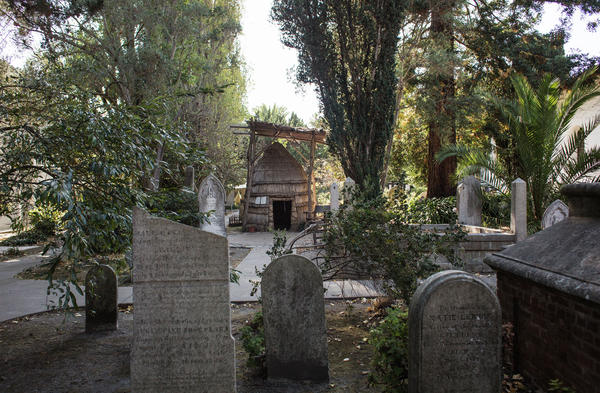 Graves and a <em>tule</em> house (Ohlone families slept in these before the arrival of missionaries) in the Mission Dolores cemetery.