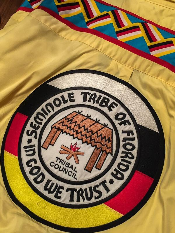 The official seal of the Seminole Tribe of Florida, in medicine colors of black, yellow, white and red.