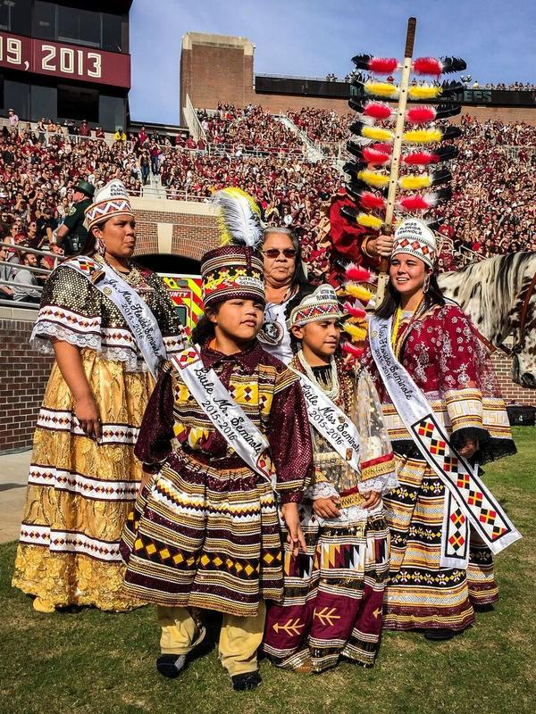 Reigning Seminole tribal royalty stand on the field at half time to crown the Homecoming King and Queen. (L to R) Skyla Osceola, Junior Miss Florida Seminole; Gregory James ll, Little Mr. Seminole; Victoria Benard, Little Miss Seminole; Wanda Bowers, director of the Miss Florida Seminole Princess Pageant; and Destiny Nunez, Miss Florida Seminole.