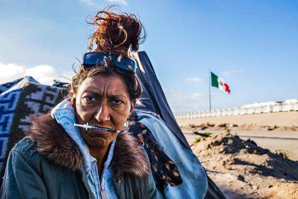 Reyna Cortiz once dreamed of being a policewoman. Outside her makeshift shelter, she holds a syringe in her mouth before injecting heroin. She has tested negative for HIV but lives in fear of contracting the virus.