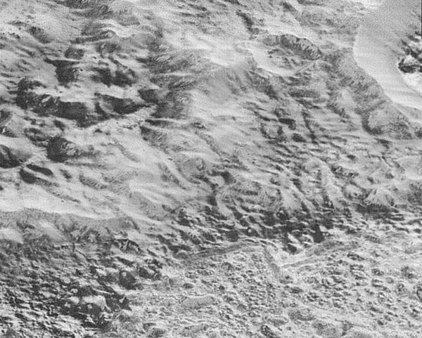 "The highest-resolution images to come from New Horizons shows what NASA calls Pluto's ""Badlands,"" an area that shows show how erosion and faulting have sculpted the icy crust into a rugged topography."