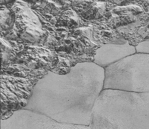 "Pluto's shoreline of Sputnik Planum is seen in the highest-resolution images yet to come from New Horizons. John Spencer of the Southwest Research Institute says the details support the idea that the mountains ""are huge ice blocks that have been jostled and tumbled and somehow transported to their present locations."""