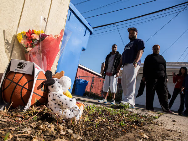 Antwan Burns-Jones, 31 (from left), William Moore, 35, and David Lee, 23, add a basketball to the memorial for Tyshawn Lee, 9, who was fatally shot in Chicago's Gresham neighborhood.