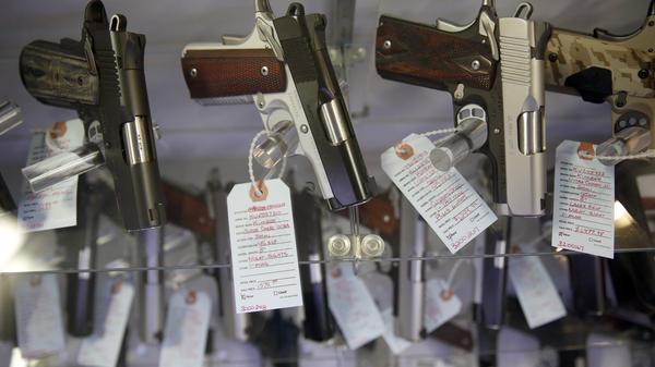 Handguns sit in a glass display case at Metro Shooting Supplies in Bridgeton, Mo.