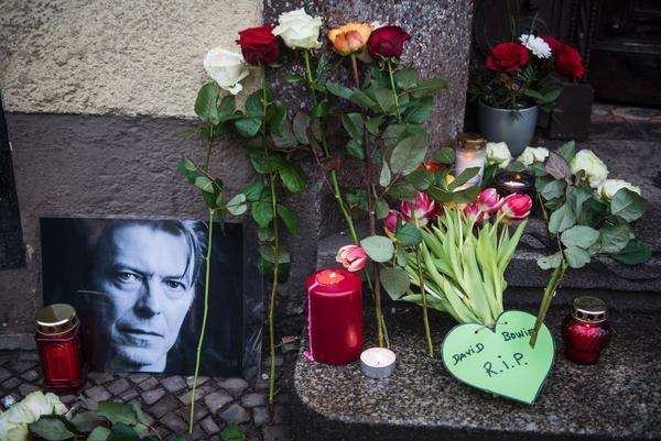 Tributes to the British rock legend are seen outside his former home in Berlin on Monday. Bowie died after a long battle with cancer, according to his official Twitter and Facebook accounts.