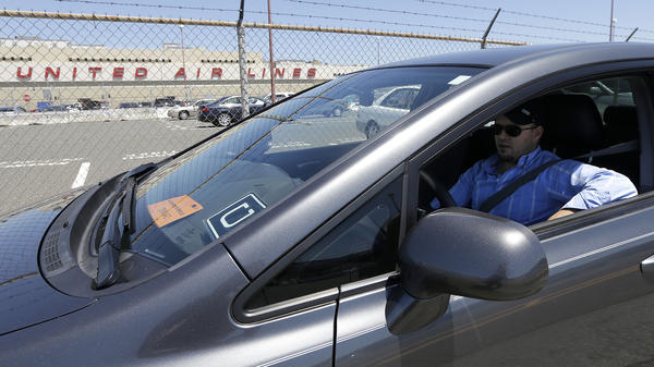 Uber driver Karim Amrani sits in his car parked near the San Francisco International Airport in July.