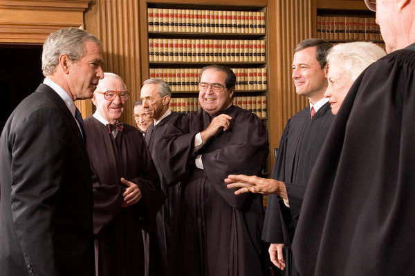 President George W. Bush (left) enjoys a light moment with members of the Supreme Court, including Justice Scalia (center) during the investiture ceremony of Chief Justice John Roberts in the Chief Justice's Conference Room in 2005.
