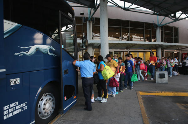 Central American immigrants just released from U.S. Border Patrol detention board a bus for Houston and then other U.S. destinations on July 25, 2014, in McAllen, Texas. Federal agencies have been overwhelmed by tens of thousands of immigrant families and unaccompanied minors from Central America crossing illegally into the U.S.