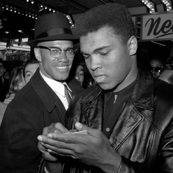 Muhammad Ali, world heavyweight boxing champion, stands with Malcolm X (left) outside the Trans-Lux Newsreel Theater in New York in 1964.