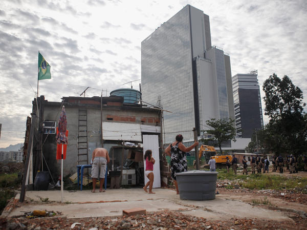 With the Olympics just months away, many wonder whether hosting the Games will be worth the effort. Here, members of the Lopes family watch during the demolition of a building in Rio's Vila Autodromo favela, with new Olympic Park structures in the background, on Feb. 24.
