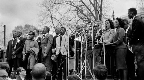 "Civil rights leaders, including Dr. Martin Luther King, Jr., sing ""We Shall Overcome"" at the conclusion of the Selma to Montgomery civil rights march in 1965."