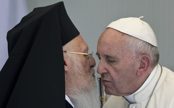 Pope Francis (right) embraces Patriarch Bartholomew I, spiritual leader of the world's Orthodox Christians, during their joint visit to a center for migrants on the Greek island of Lesbos on Saturday. Both called on Europe to show greater compassion in dealing with migrants.