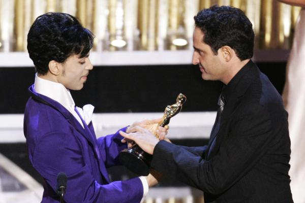 """Uruguayan singer Jorge Drexler receives the Oscar from Prince after """"Al Otro Lado del Rio"""" from <em>The Motorcycle Diaries</em> won best original song at the 77th Academy Awards in 2005."""